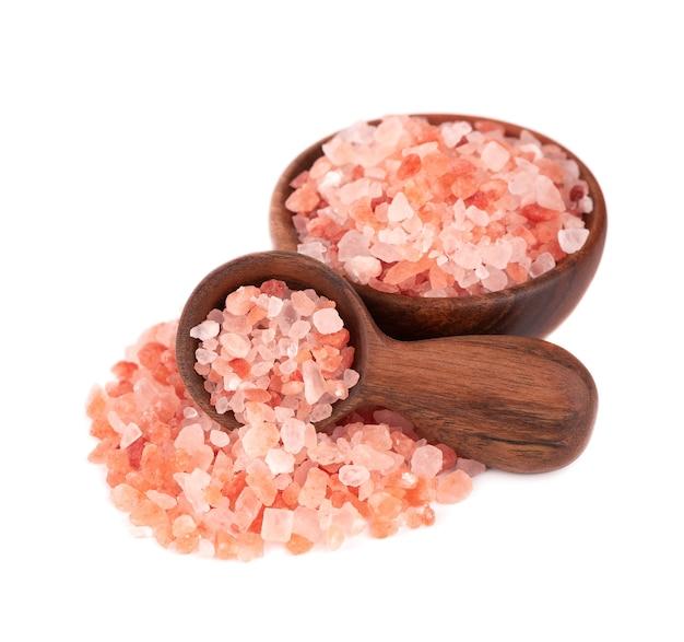 Sól himalajska różowa w drewnianej misce i łyżką, na białym tle
