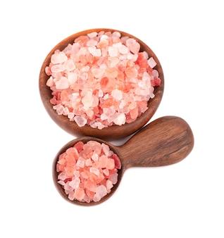 Sól himalajska różowa w drewnianej misce i łyżką, na białym tle.