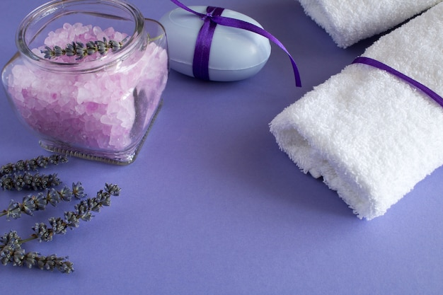 Sól lawendowa, mydło i białe ręczniki na fioletowym tle