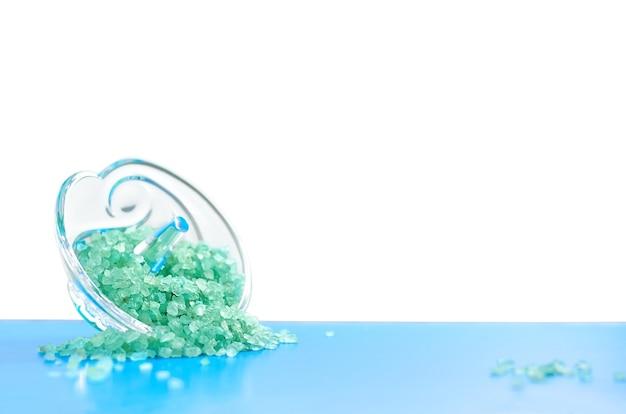 Sól morska błękitna w szklanej podstawce na niebieskiej powierzchni na białym tle na białym tle