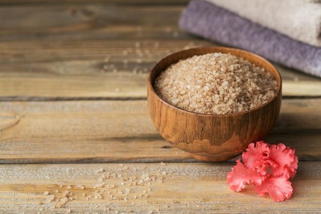 Sól morska i kolorowe ręczniki z koralowymi kwiatami azalii na rustykalnej drewnianej powierzchni. zdrowa pielęgnacja skóry, twarzy i ciała. koncepcja spa i sauny