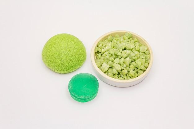 Sól morska, mydło zielonej herbaty i gąbka na białym tle