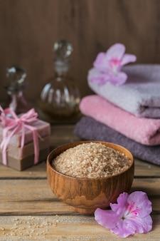 Sól morska, naturalne ręcznie robione mydło, naturalny olej kosmetyczny i kolorowe ręczniki z kwiatami azalii na rustykalnej drewnianej powierzchni. zdrowa pielęgnacja skóry, twarzy i ciała. koncepcja spa i sauny