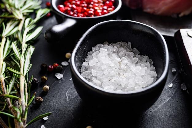 Sól morska w czarnej misce i zioła rozmarynu z bliska na czarnym kamiennym stole z bocznym widokiem przypraw selektywnej ostrości
