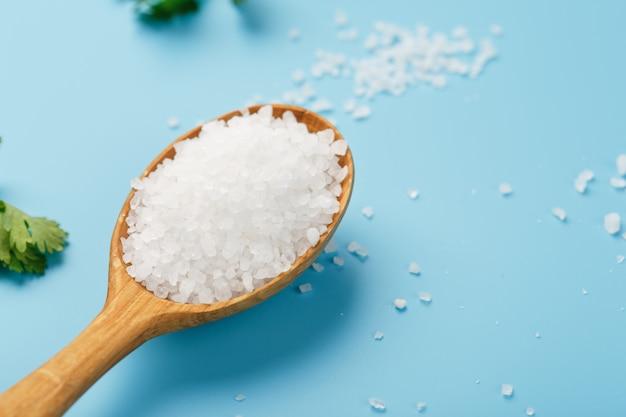 Sól morska w drewnianej łyżce na duże kryształy soli z zielenią na niebiesko.