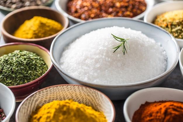 Sól oraz różne przyprawy i zioła w miseczkach.