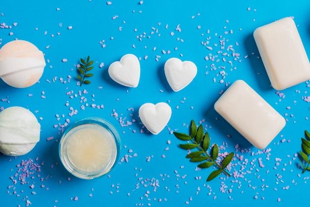 Sól rozprzestrzenia się na niebieskim tle z bombami do kąpieli; mydło i śmietanka