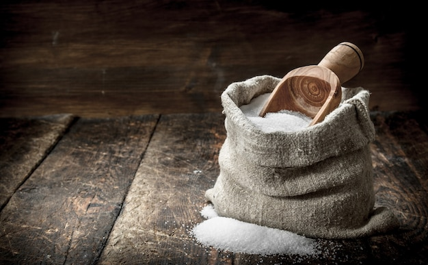 Sól w drewnianej łyżce. na drewnianym tle.
