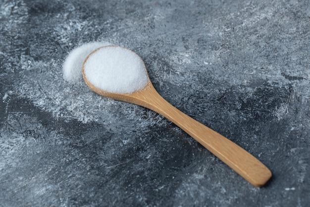 Sól w drewnianej łyżce na marmurowym tle.