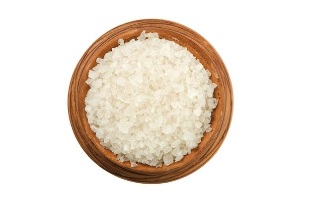 Sól w glinianej filiżance odizolowywającej na białym tle
