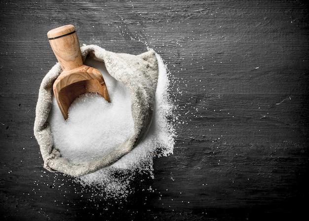 Sól w starej torbie. na czarnej tablicy.