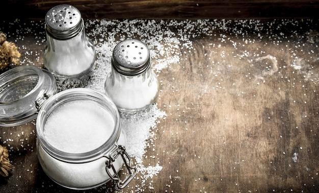 Sól w szklanym słoju na drewnianym stole. na rustykalnym stole.