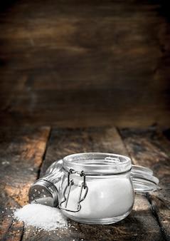 Sól w szklanym słoju. na drewnianym stole.