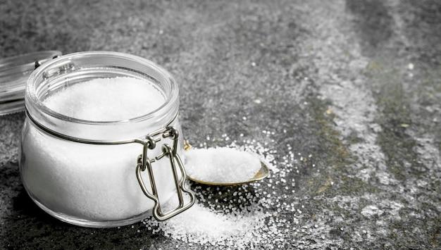 Sól w szklanym słoju. na tle rustykalnym.