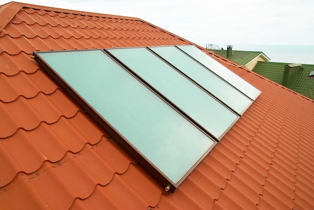 Solarny system ogrzewania wody na czerwonym dachu domu.
