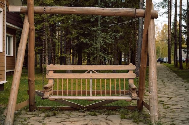 Solidne drewniane huśtawki ogrodowe obok drewnianego domu na wsi