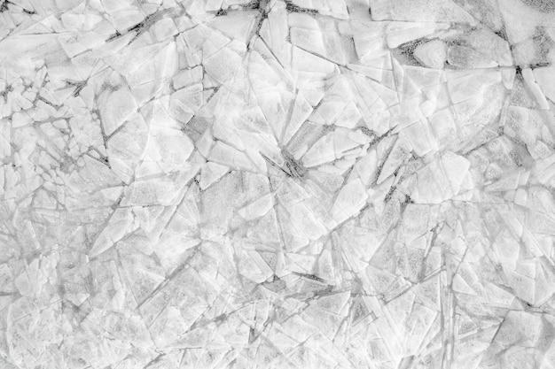 Solidne tło z kawałków lodu i kryształków śniegu z pęknięciami i teksturą