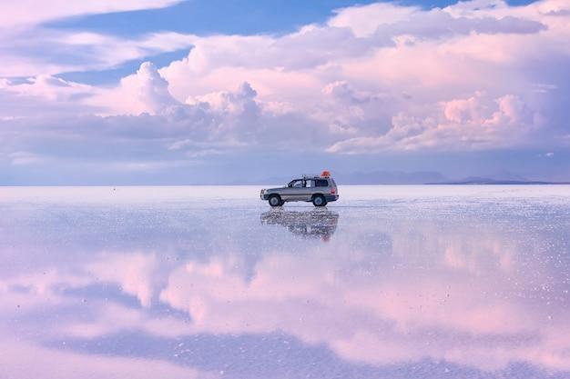 Solne mieszkanie uyunu o zachodzie słońca z dramatycznymi chmurami i odbiciem boliwia ameryka południowa south