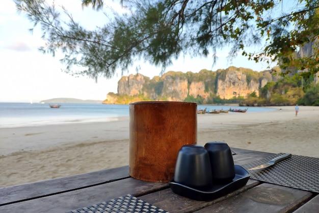Solniczka pieprzniczka i serwetki na drewnianym stole na piaszczystym brzegu tropikalnej wyspy w pobliżu morza