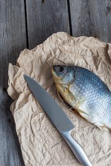 Solona sucha ryba vobla z ostrym nożem na zmiętym papierze rzemieślniczym na drewnianej, pysznej przekąsce do piwa
