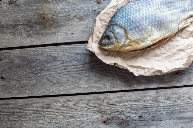 Solone dry fish vobla na zmiętym papierze rzemieślniczym na drewnianym