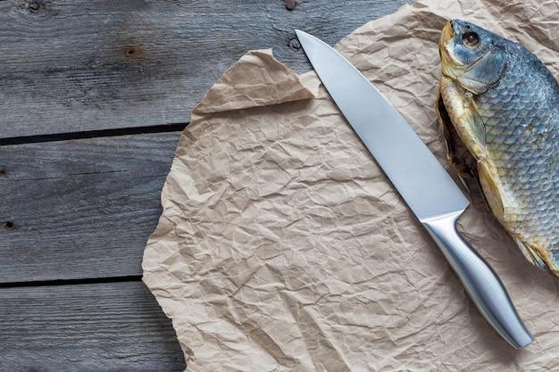 Solone dry fish vobla z ostrym nożem na zmiętym papierze rzemieślniczym na drewnianym