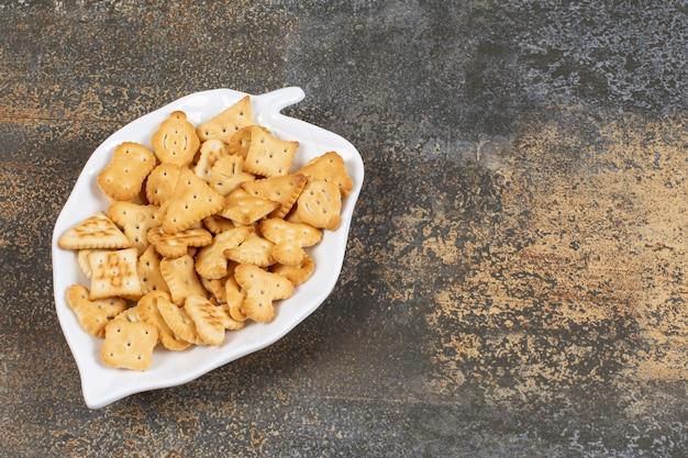 Solone krakersy o różnych kształtach na talerzu w kształcie liścia.