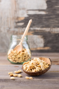 Solone orzeszki ziemne w misce iw słoiku na drewnianym stole. zdrowe wegetariańskie jedzenie. styl rustykalny. widok pionowy