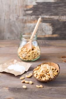Solone orzeszki ziemne w misce iw słoiku z łyżką i solą na papierze na drewnianym stole. zdrowe wegetariańskie jedzenie. styl rustykalny. widok pionowy