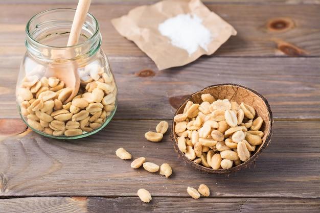 Solone orzeszki ziemne w misce iw słoiku z łyżką i solą na papierze na drewnianym stole. zdrowe wegetariańskie jedzenie. styl rustykalny