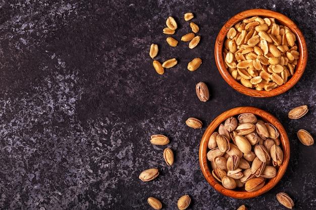 Solone pistacje i orzeszki ziemne na kamiennej powierzchni
