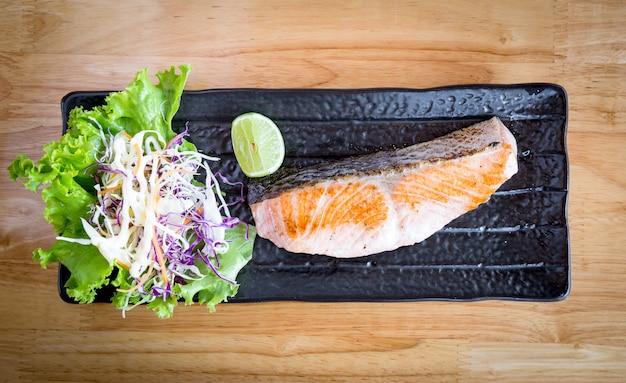Solony łosoś z grilla podawany z cytryną i sałatką na czarnym talerzu ceramicznym na drewnianym stole z miejscem na kopię.