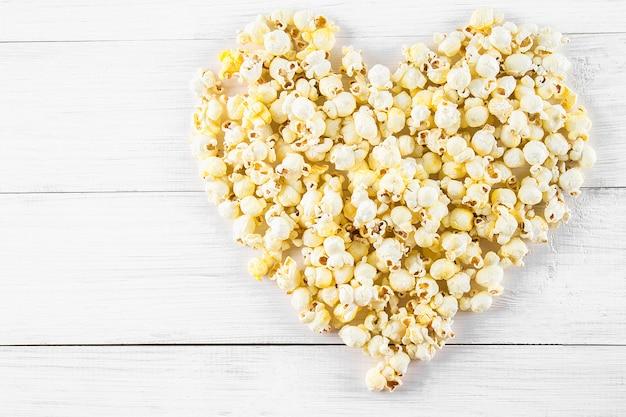 Solony popcorn w kształcie serca na białym stole. widok z góry.