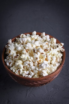 Solony popcorn w misce na stole na szarym tle. przedni widok.