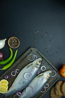 Solony śledź z cebulą i ziołami na desce do krojenia