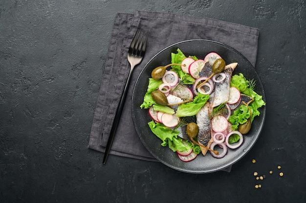 Solony śledź z przyprawą, kaparami, ziołami i sałatką z cebuli na czarnej płycie na ciemnym tle z miejsca kopiowania. marynowana pokrojona ryba. jedzenie ze zdrowymi tłuszczami nienasyconymi, płasko leżące