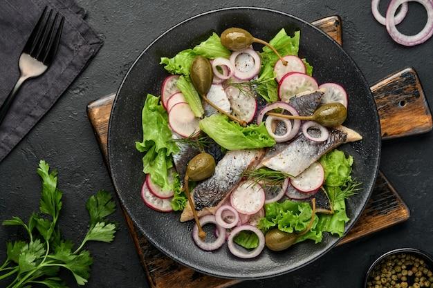 Solony śledź z przyprawą, kaparami, ziołami i sałatką z cebuli na czarnym talerzu na ciemnym tle