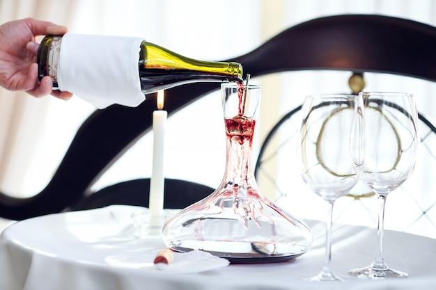 Sommelier wlewający czerwone wino do karafki