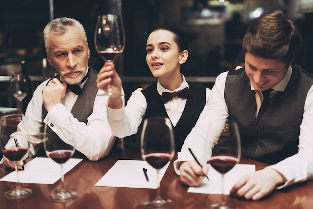 Sommeliers to two men and woman in restaurant.
