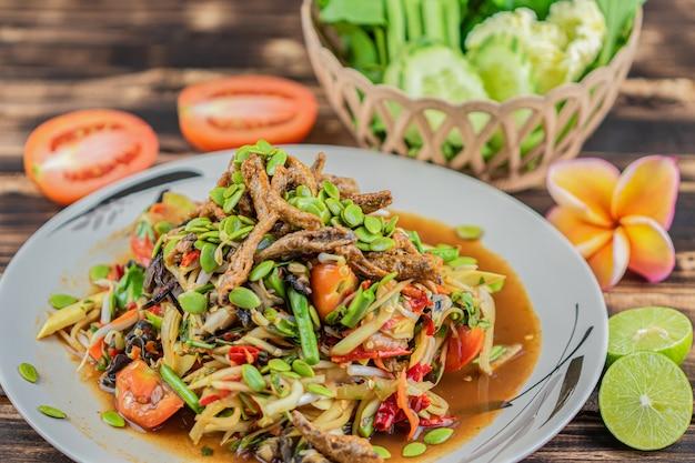 Somtum. tajska pikantna zielona papaja sałatka na drewnianym stole. (somtum pha)