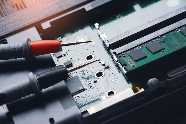 Sonda multimetru umieszczona na płycie głównej laptopa
