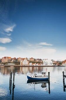 Sonderborg, dania: mała biała łódź rybacka na tle starego europejskiego miasta