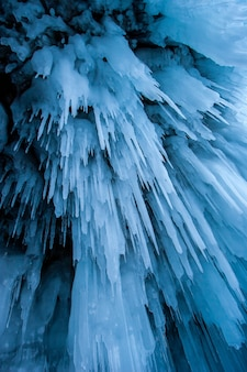 Sople niebieskiego lodu w jaskini nad jeziorem bajkał. długie sople zwisają jak stalaktyty. pionowy.