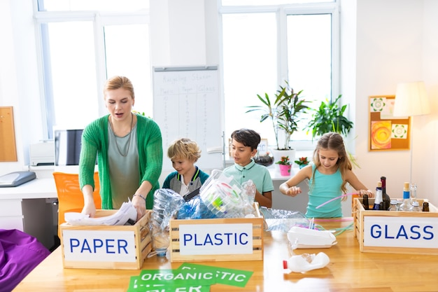 Sortowanie śmieci razem. trzech uczniów i ich nauczycielka ekologii wspólnie sortują śmieci na lekcji