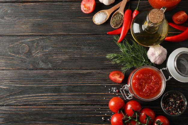 Sos chili, czosnek, pomidory czereśniowe, oliwa z oliwek, przyprawy na drewniane tła, miejsca na tekst. widok z góry