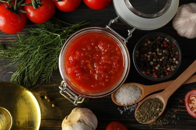 Sos chili, czosnek, pomidory czereśniowe, oliwa z oliwek, przyprawy na drewniane tła, z bliska. widok z góry