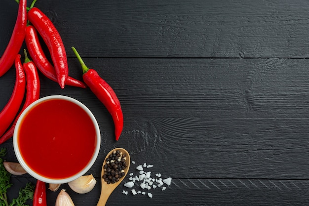Sos chili i papryka na ciemnej powierzchni drewnianej