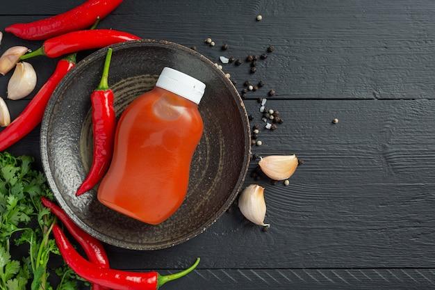 Sos chili w butelce i papryki na ciemnej powierzchni drewnianych