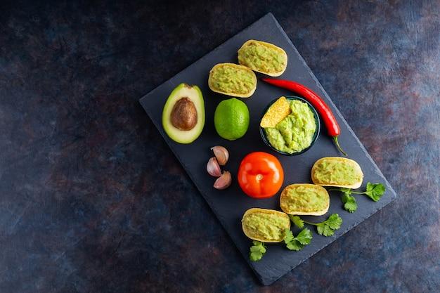 Sos guacamole, chipsy nachos i składniki na ciemnym tle