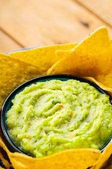 Sos guacamole i chipsy nacho. chipsy tortilla i meksykański sos guacamole w misce. zbliżenie